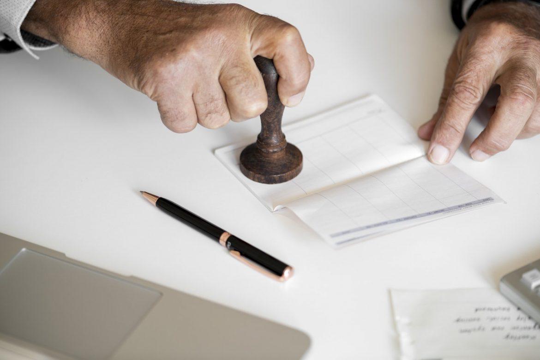 Bank Official Verifying A Check